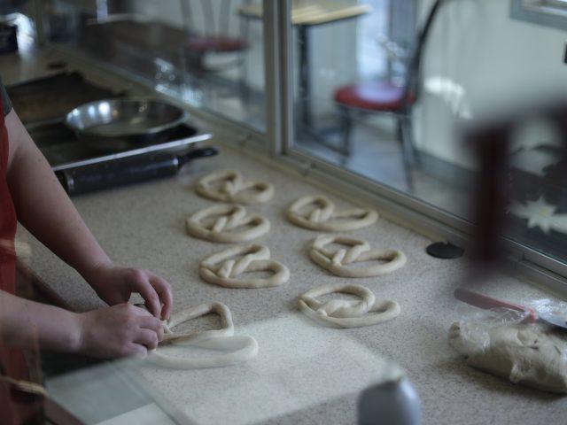 baker shaping handmade soft pretzels