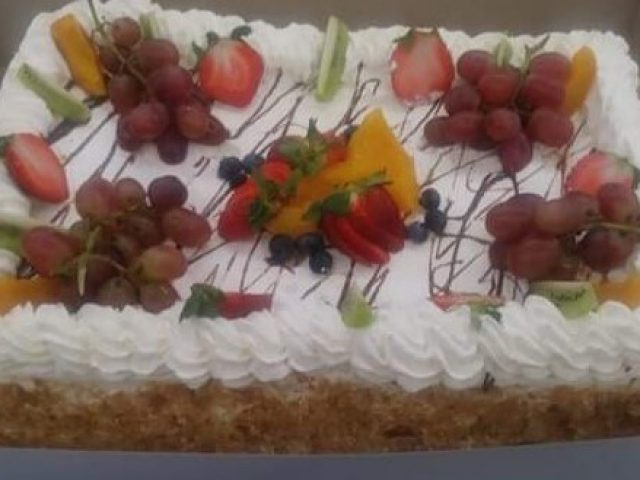 homemade sponge cake with vanilla icing and fruit on the top