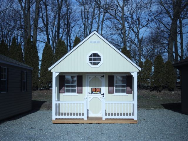 white storage shed with a porch nook and a for sale sign hanging on the front door